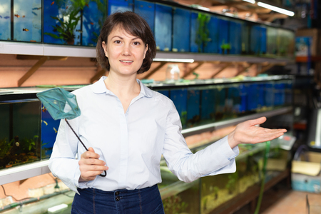 Attractive polite saleswoman standing near rows of fish tanks in pet store Stock fotó