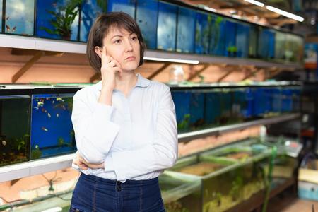 Portrait of pensive woman visiting pet store in search of exotic aquarium fish