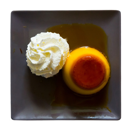 Image of tasty dessert cream flan served with butter cream  at black plate. Isolated over white background