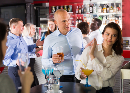Tipsy man trying to seduce young female colleague on office party at nightclub