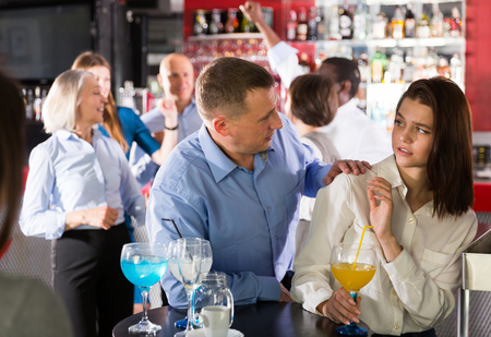 Disgruntled young woman gesturing stop to male colleague flirting with her during firms party Imagens
