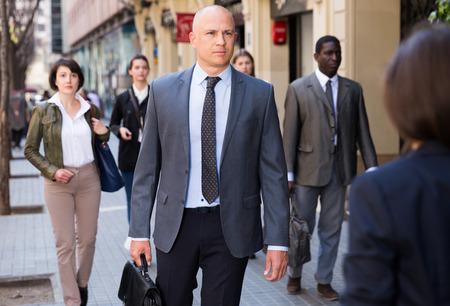 Adult male businessman in formal wear walking down street in downtown