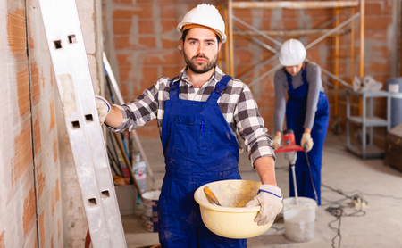 Portrait of builder in process of finishing work in cottage Stock Photo