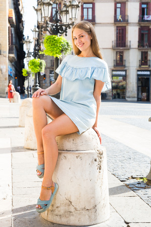 Attractive smiling girl in lightweight blue dress sitting on stone bollard in historical center of Barcelona Standard-Bild