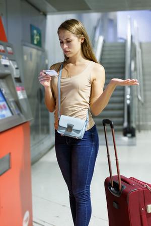 Junge Frau mit Gepäck mit Fahrkartenautomat an der U-Bahn-Station Standard-Bild