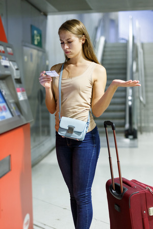 Young woman with luggage using ticket vending machine at metro station