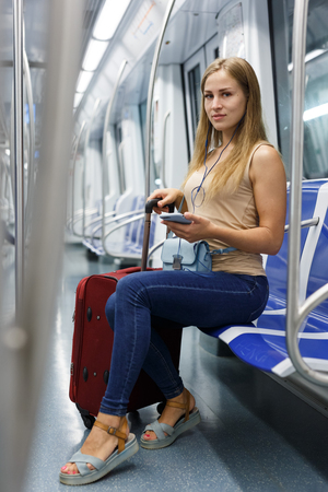 Young woman traveling on underground and listening music with headphones 版權商用圖片