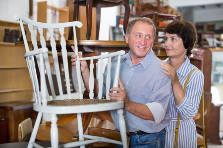 Mature man with his wife are choosing an old chair in antique shop. Focus on both persons