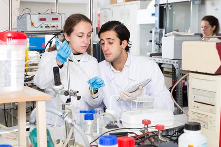Zwei feine Labortechniker diskutieren während der Arbeit mit Reagenzien in Reagenzgläsern während des chemischen Experiments Standard-Bild