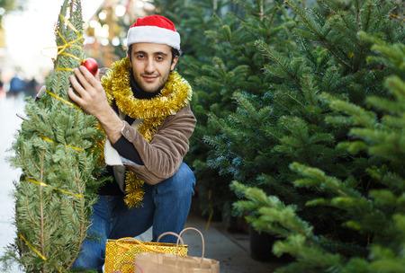 Young man choosing decorations and Christmas tree at Christmas market
