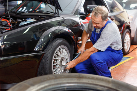 Elderly glad  cheerful positive man mechanic engaged in replacement of car wheel in auto workshop