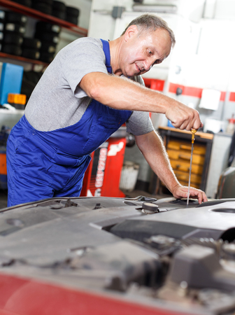 Skilled mature car mechanician changing motor oil in vehicle in auto repair shop Imagens - 121690292