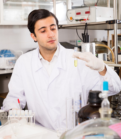 Portrait of young focused lab technician writing report on results of chemical experiments in notebook
