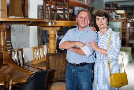 Mature man with his wife are choosing the furniture at antique shop. Focus on both persons Фото со стока