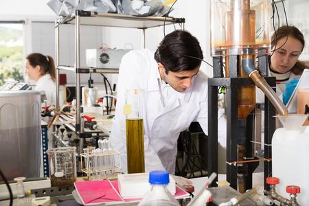 Adult man chemist working in laboratory, analyzing liquid samples in test flasks