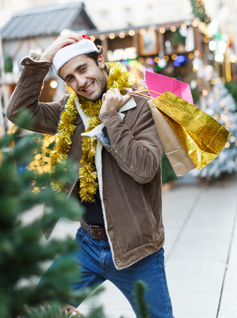 Portrait of young man in Christmas  hat  with purchases  at Christmas market