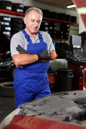 Pensive elderly man mechanic looking at car in auto workshop, determining scope of work