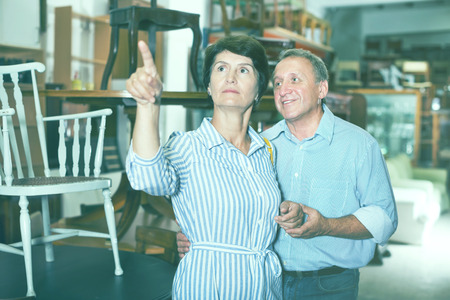 Mature man with his wife are choosing old chair in a antique shop. Focus on both persons