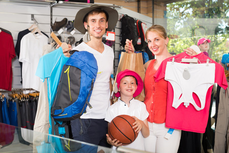 Cheerful parents with boy in school age shopping hiking goods in sport store Stok Fotoğraf