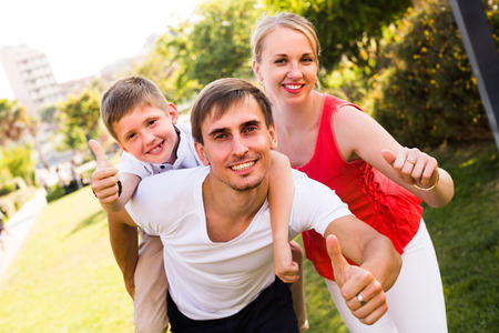 joyful young family of three having fun in park on summer day and holding thumbs up Imagens