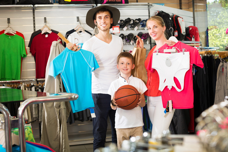 Glad young family of three picking various clothing in sport department Фото со стока - 121721882