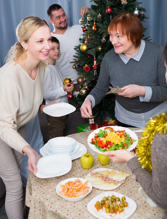 Large friendly family serving meals on table for Christmas dinner and decorating Christmas tree Imagens