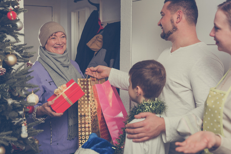 Grandmother coming to congratulate her children and grandson on New Year or Christmas