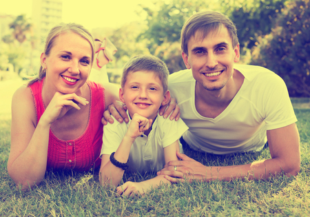 joyful smiling family of three lying on the grass in city park in  summer day