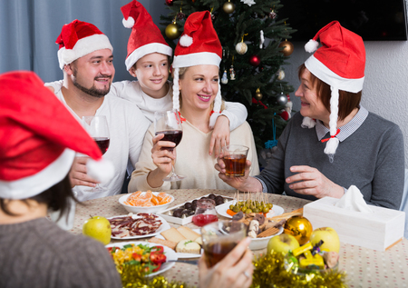 Portrait of large friendly family during celebration of New Year at table at home