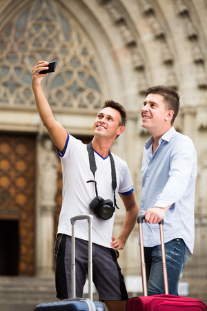 Two happy guys with luggage  taking selfie in city at summer day