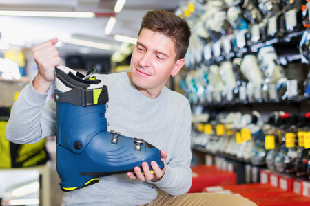 Customer male is trying on new boots for skiing in store Banque d'images