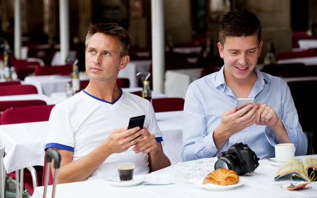 Cheerful guys looking at smartphones and drinking coffee with bakery Imagens