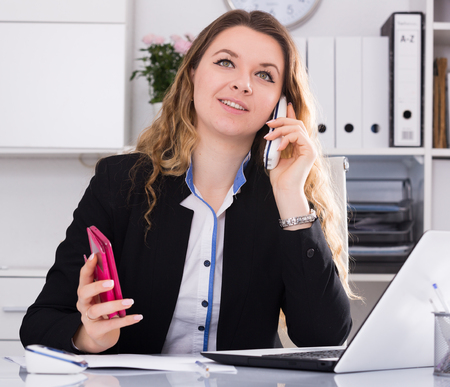 Young and smiling woman office worker talking on the phone