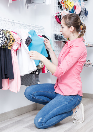 Young female is choosing clothes for kid in the child clothes boutique