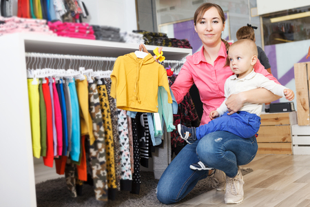 glad woman with her kid are choosing clothes in child store.