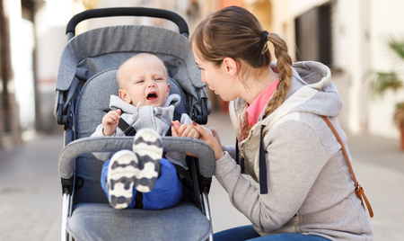 young mother calming a crying child sitting in a stroller while walking down the street