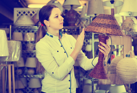 Cheerful  woman is choosing new lamp for her home in the store. Stockfoto