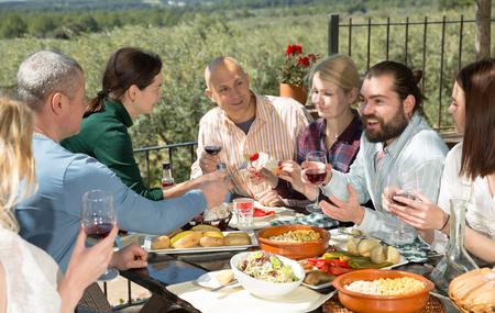 Une entreprise de six personnes passe du temps à déjeuner sur une terrasse en plein air Banque d'images