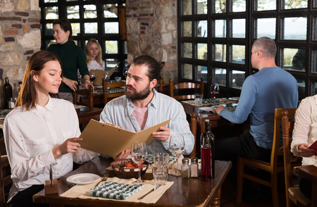 Young pleasant couple choosing dishes out of menu card in country style restaurant