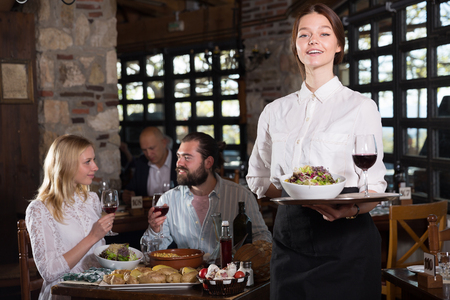Professional waitress greeting customers at table in rustic restaurant 스톡 콘텐츠