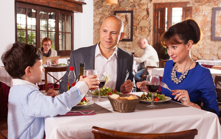 Portrait of cheerful family with little son having dinner at restaurant