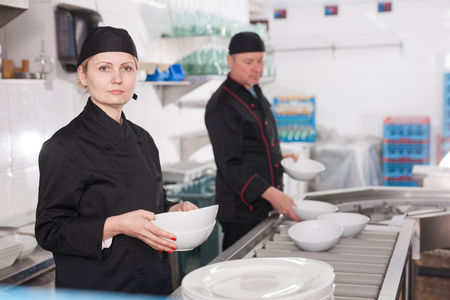 Woman working in restaurant kitchen, preparing clean plates for setting on tables
