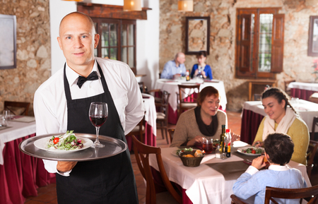 Positive waiter with tray in foreground and visitors having dinner at restaurant on background