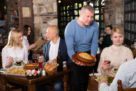 Friendly adult waiter bringing delicious meals to visitors of cosy rustic style restaurant