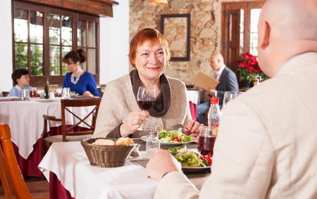 Portrait of happy senior woman and her adult son having dinner in restaurant Imagens