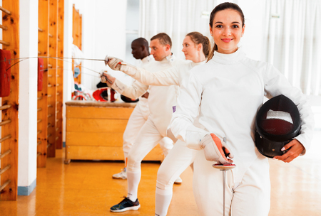 Smiling  positive glad  sporty young woman in uniform standing at fencing workout