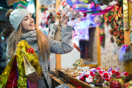 Young positive satisfied woman at fair near counter with Christmas gifts in evening time