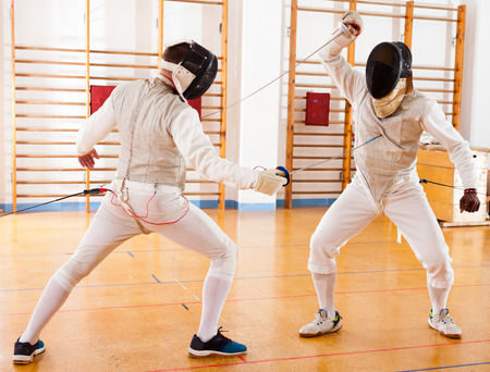 Group of fencers at fencing workout, exercising the techniques in battle