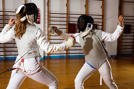 Two positive smiling female fencers  exercising movements in duel at fencing room 写真素材