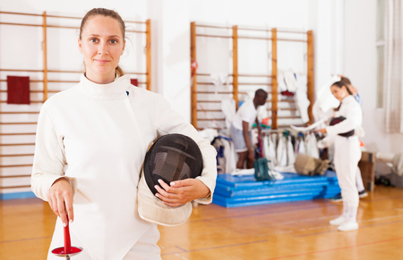 Smiling sporty young woman in uniform standing at fencing workout